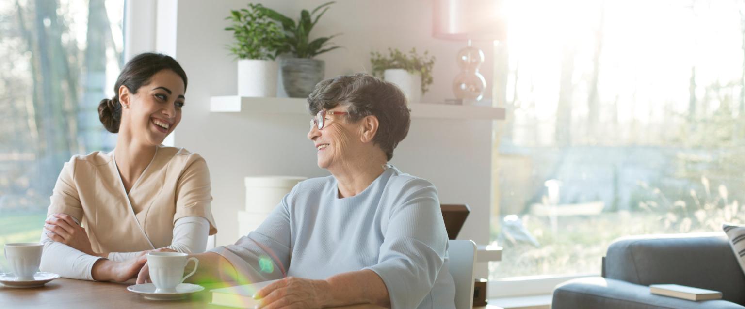 Close up caregiver holding senior hands.