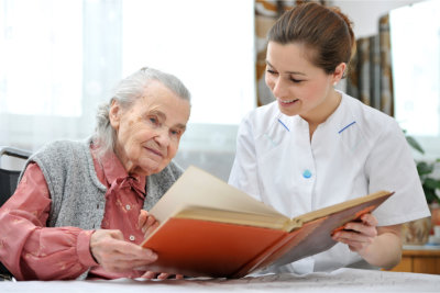 Caregiver assisting an elderly woman to read a book